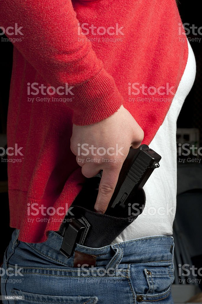 Yound Woman Drawing From an Inside-the-Waistband Holster royalty-free stock photo