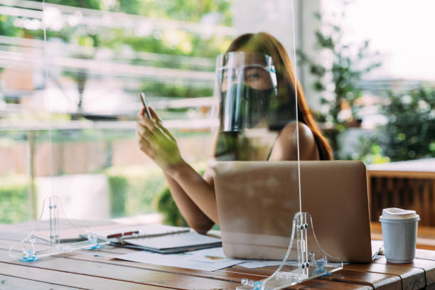 Young 20s Asian beautiful woman wearing a protective face shield and mask with partition in cafe restaurant. While using computer laptop and mobile phone outside. - Corona Virus prevention concept stock photo