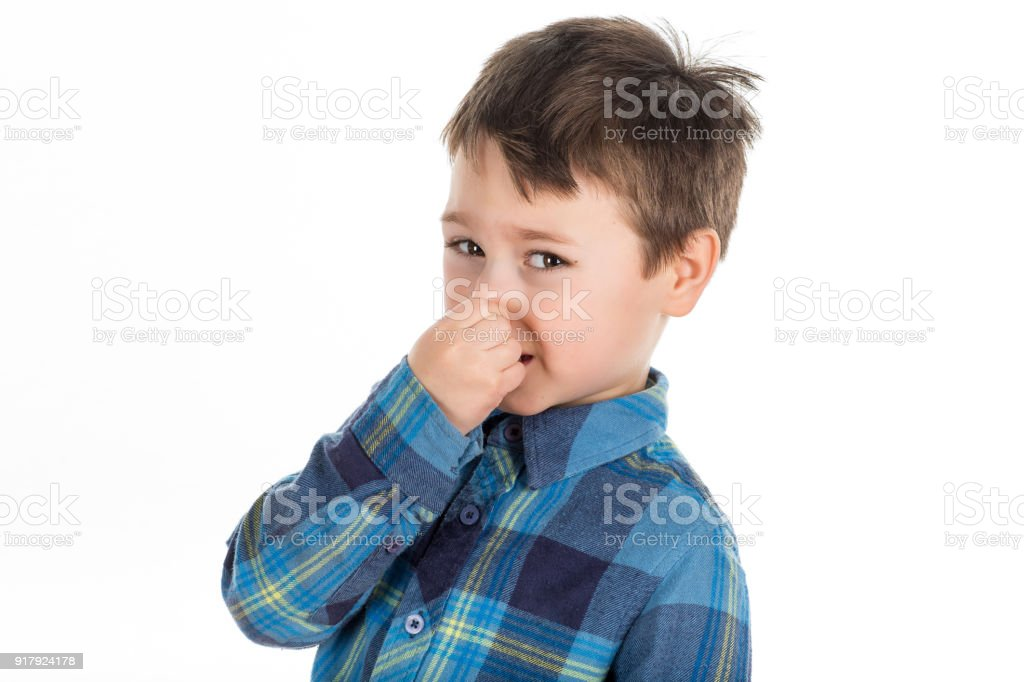 Young 5 years old boy holding his nose on a white background. stock photo