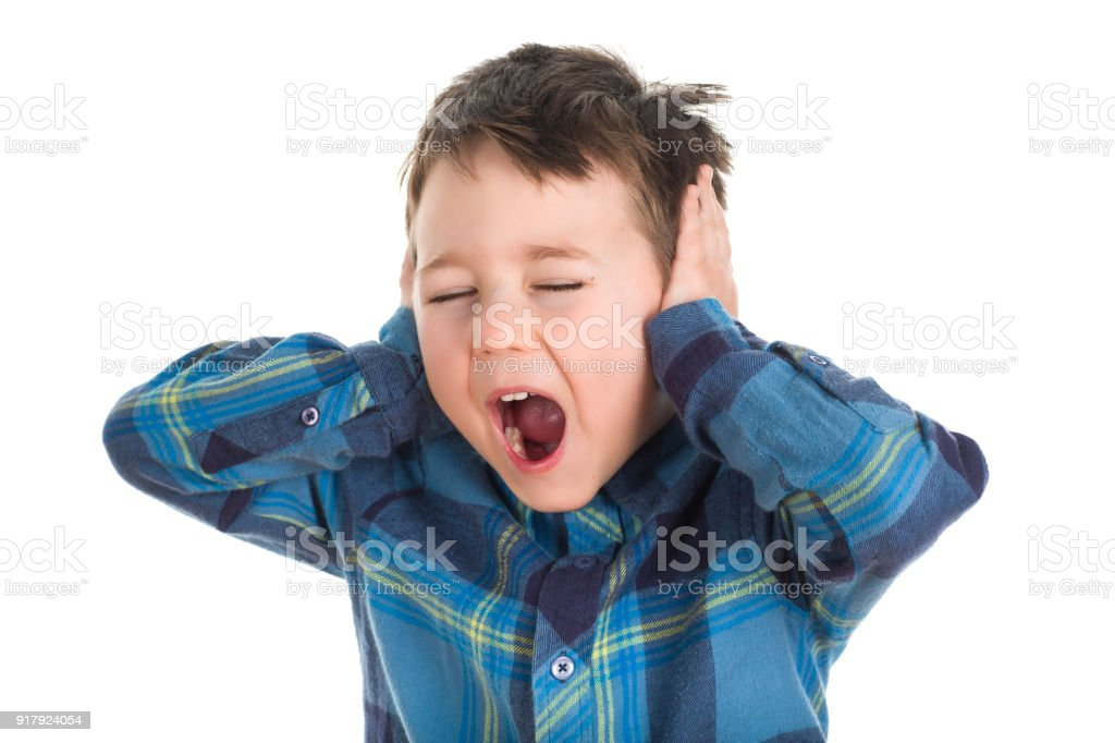 Young 5 years old boy screaming and covering ears stock photo