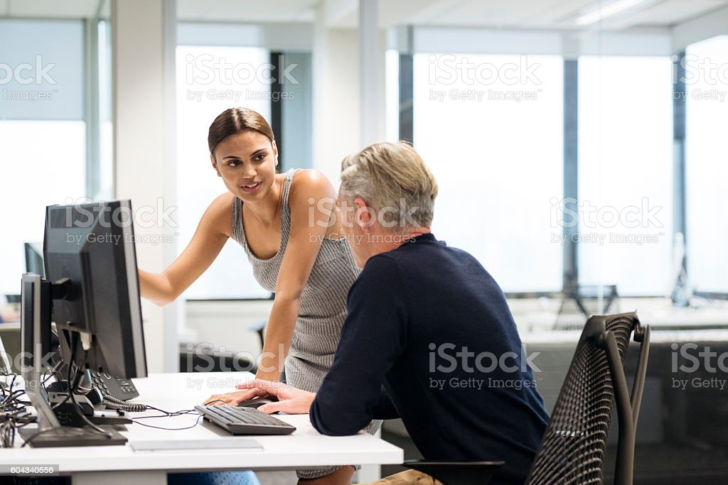 Young Aboriginal Australian businesswoman in office with male colleague stock photo