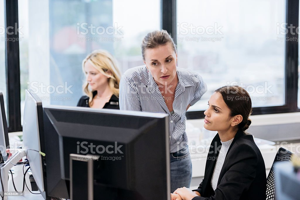 Young Aboriginal Australian woman in office with business colleague stock photo