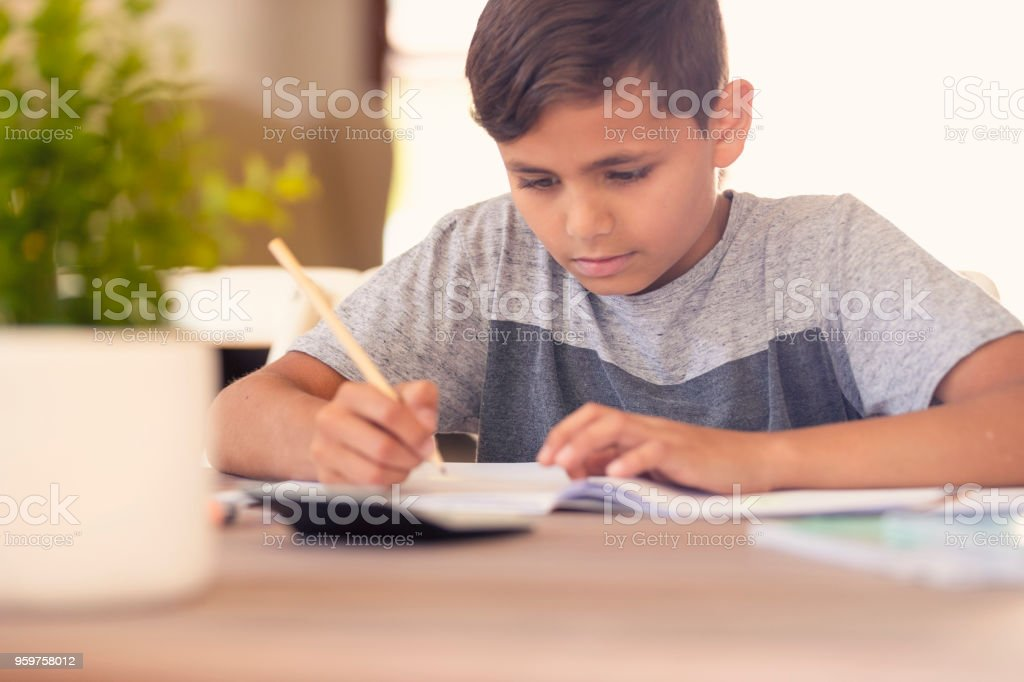 Young Aboriginal boy doing homework. stock photo