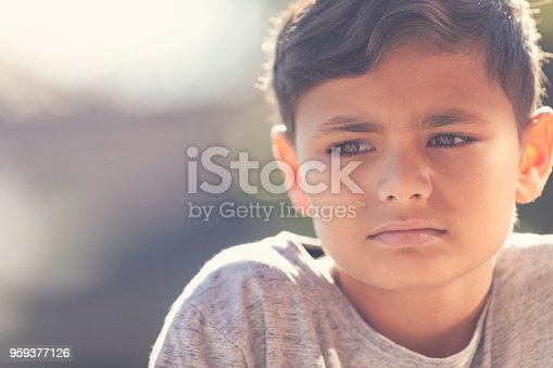 Young Aboriginal boy portrait. He is sad and unhappy and looking away from the camera.