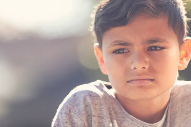 Young Aboriginal boy portrait. Young Aboriginal boy portrait. He is sad and unhappy and looking away from the camera. hungry child stock pictures, royalty-free photos & images