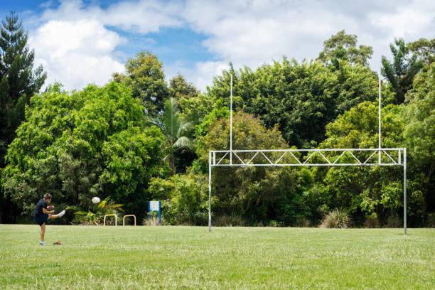Young Aboriginal Boy Practising Rugby Goal Kicking stock photo