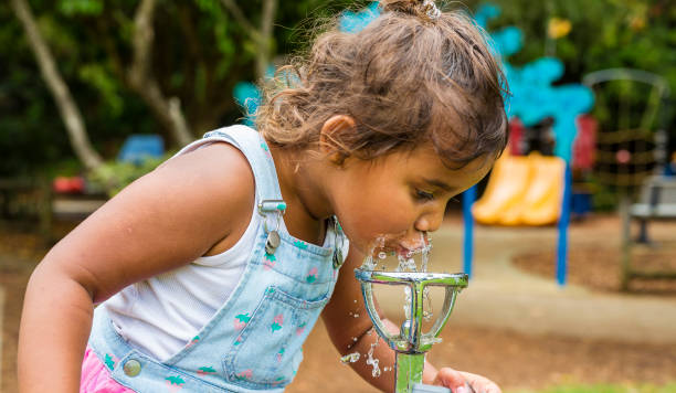 Young Aboriginal Girl Drinking From a Water Fountain stock photo