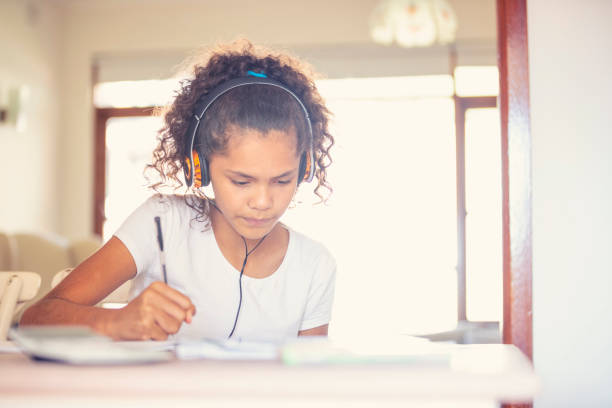 Aboriginal jungen Mädchen mit Kopfhörern zu studieren. – Foto