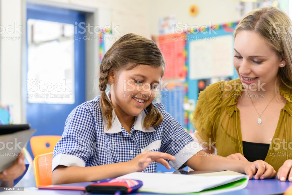 Young Aboriginal girl using digital tablet with her teacher helping stock photo