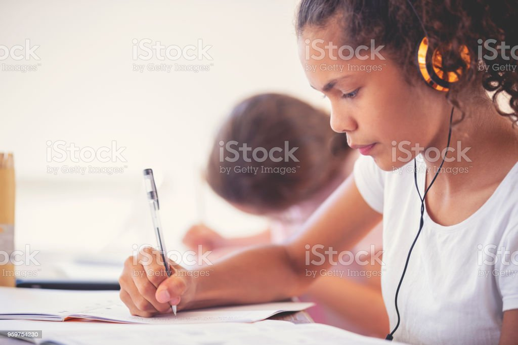 Young Aboriginal girls studying with headphones. stock photo