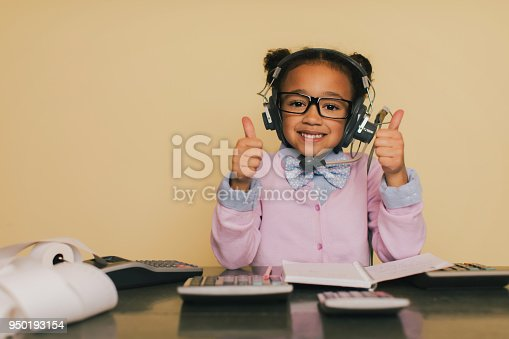 A young accountant girl in bow ties sits at her desk at work. She sits in front of a calculator. She is super busy at tax season, but smiles because she loves to be a financial advisor and help others with their business.