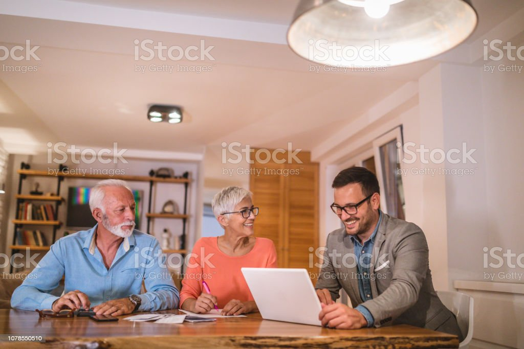 Young accountant helping a senior couple with finances - foto stock