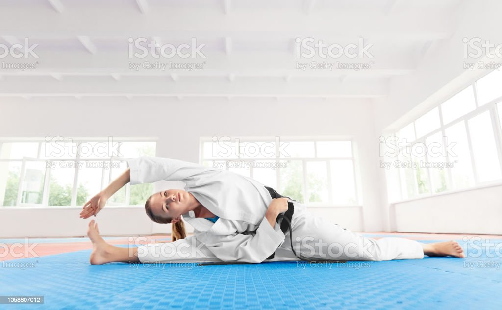 Young active girl wearing in white kimono with black belt, doing...