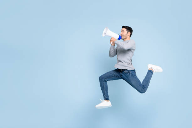 Young active man jumping and shouting on megaphone isolated on light blue background with copy space stock photo