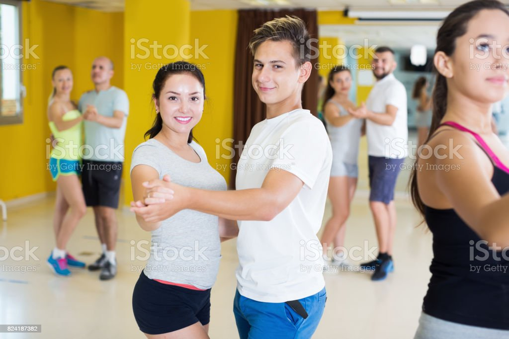 Young active men and women dancing bachata stock photo