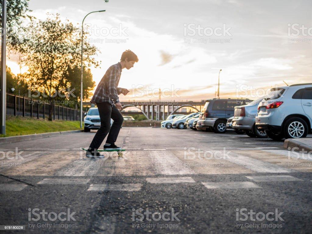 jeune adolescent actif le skateboard à cheval sur le passage piéton en milieu urbain ville - Photo