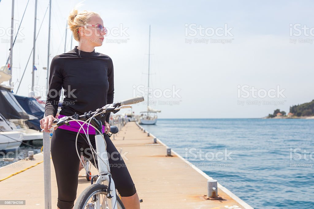Young active woman cycling on pier in marina. – Foto