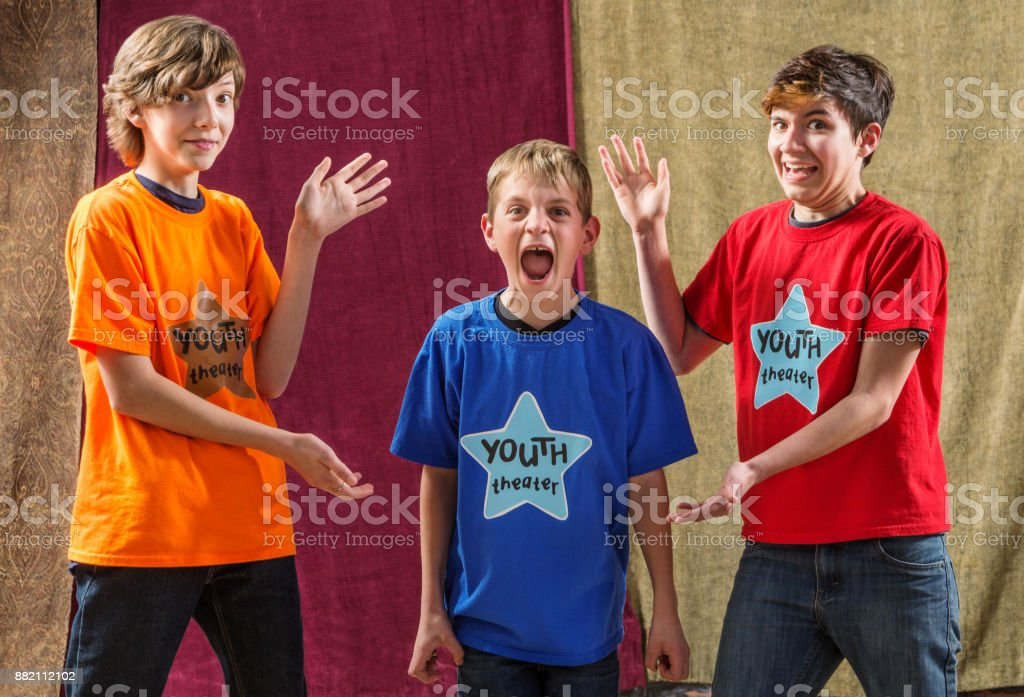 Young actor screams beside two friends stock photo