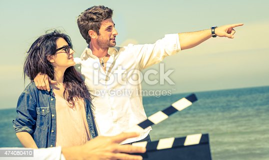 istock Young actors couple in love acting for romantic film beach 474080410