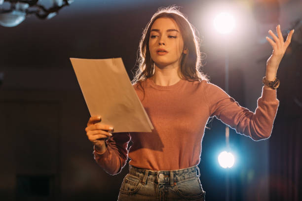 young actress reading scenario on stage in theatre young actress reading scenario on stage in theatre performing arts event stock pictures, royalty-free photos & images