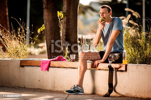 Young disabled athletic man sitting on a park bench and taking a break after exercising in a public park, eating an apple. Towels, fruit juice and a fruit cup with berries are next to him.
