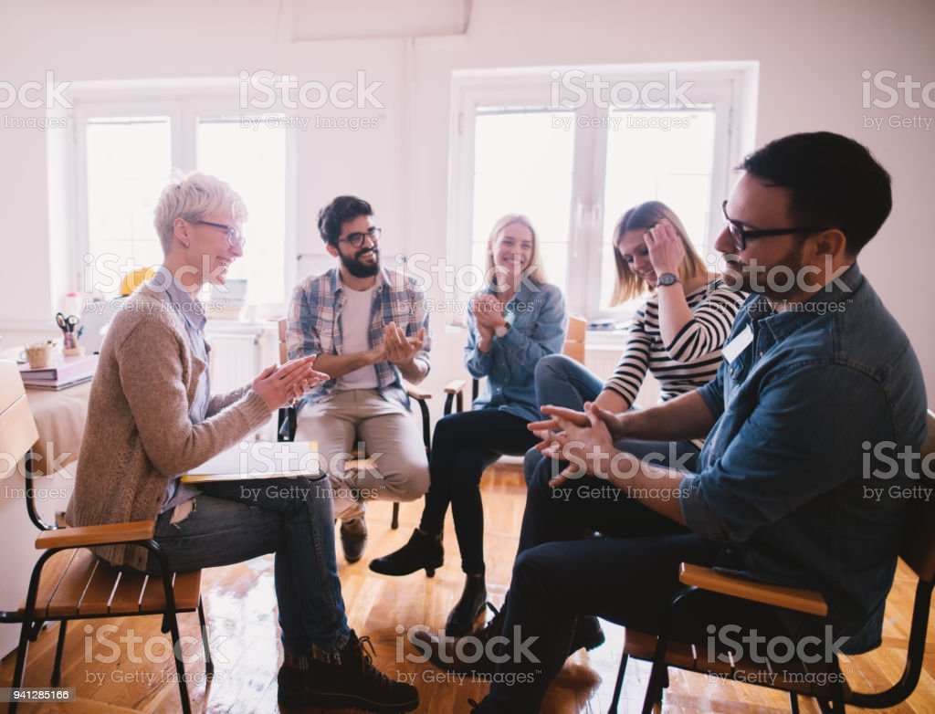 Young addicted people having celebrating situation while sitting together on special group therapy. Brave persistent guy getting applause after his confession and progress. royalty-free stock photo