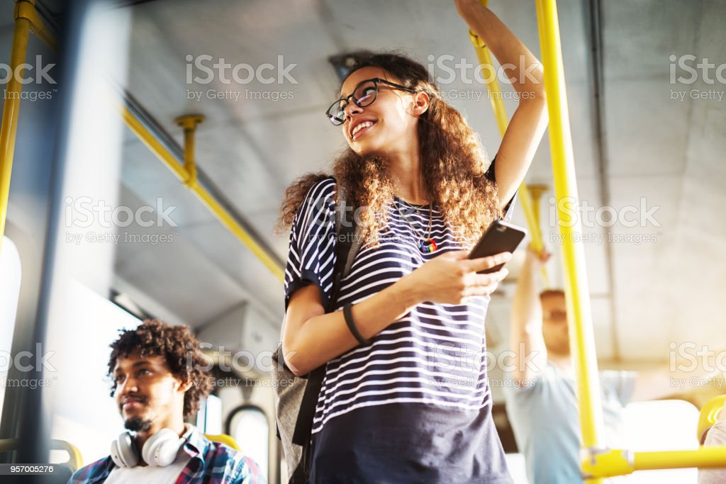 Young adorable joyful woman is standing on the bus using the phone and smiling. stock photo
