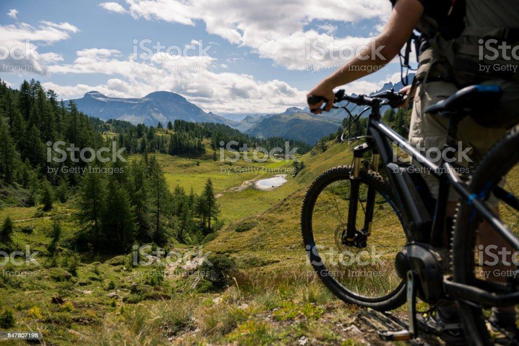 Hombre activo adulto joven en montaña con casco para bicicleta y mochila mirando el panorama escénico con bicicletas eléctricas en día soleado de verano al aire libre - foto de stock