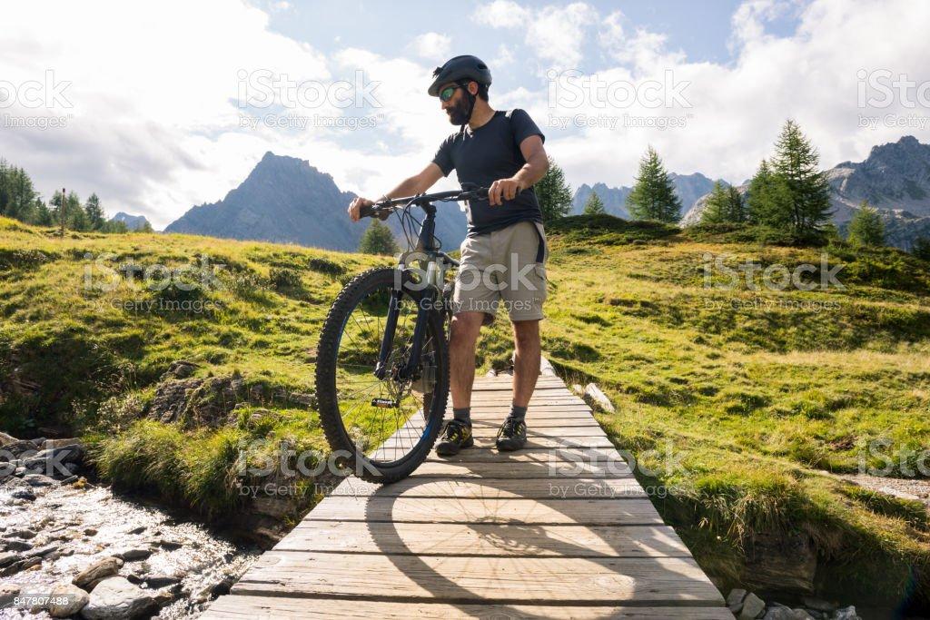 Hombre activo adulto joven en el pequeño puente de madera de montaña llevaba casco de bicicleta en río con bicicletas eléctricas en día soleado de verano al aire libre - foto de stock