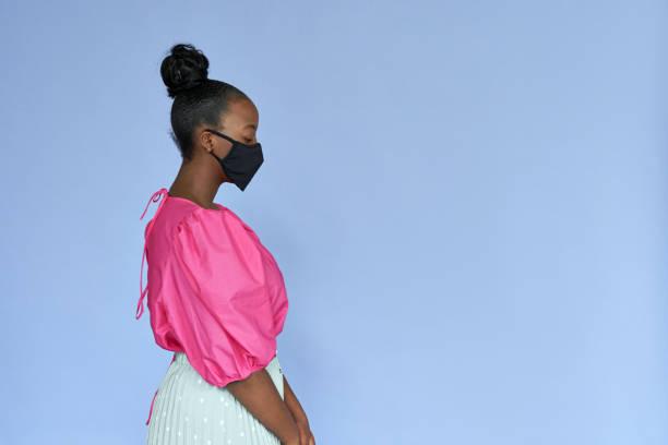 スタイリッシュなトレンディなファッション服と黒い綿を身に着けている若い大人のアフリカ系アメリカ人女性は、ライラックバイオレットモーヴスタジオの背景に孤立した立って医療フェ� - gen z ストックフォトと画像