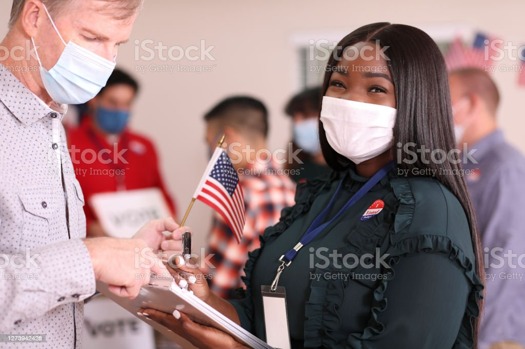 Young adult, African descent woman works polling place wearing mask. African descent, young adult woman works at polling place in the USA election wearing a protective mask to protect herself against COVID-19 or other infectious diseases. 2020 Stock Photo