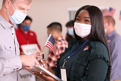 Young Adult African Descent Woman Works Polling Place Wearing Mask Stock Photo - Download Image Now