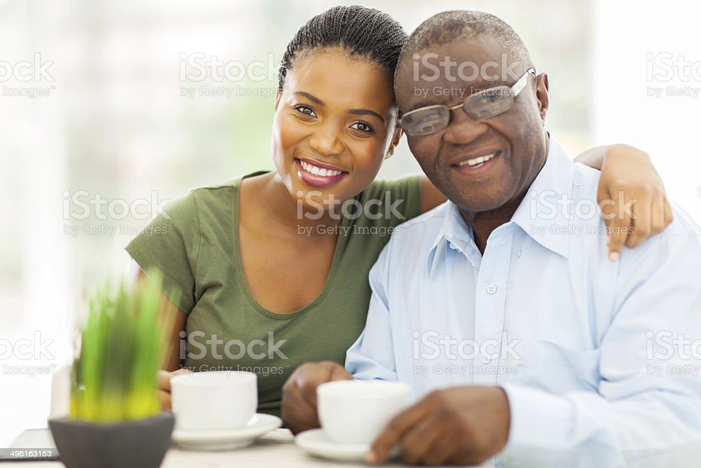 young adult african girl and father having coffee stock photo