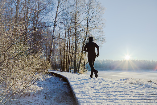 Young, adult alone man in tracksuit and hat running on forest trail in sunny winter morning after first snow. Enjoying sport in sunrise. Daily active lifestyle. Life motion. Back view.