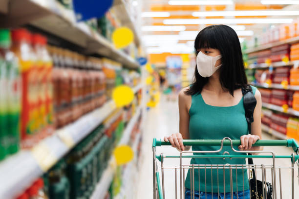 Young adult Asian woman wearing a face mask while shopping with cart trolley in grocery supermarket store. stock photo