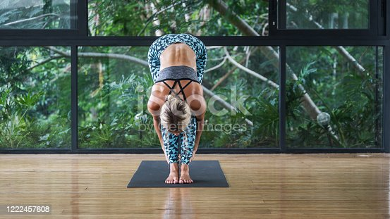 Concept of flexibility and stretching. Panoramic view of young adult athletic woman standing in head to knee position, practicing yoga in gym class, training on mat in room with copy space