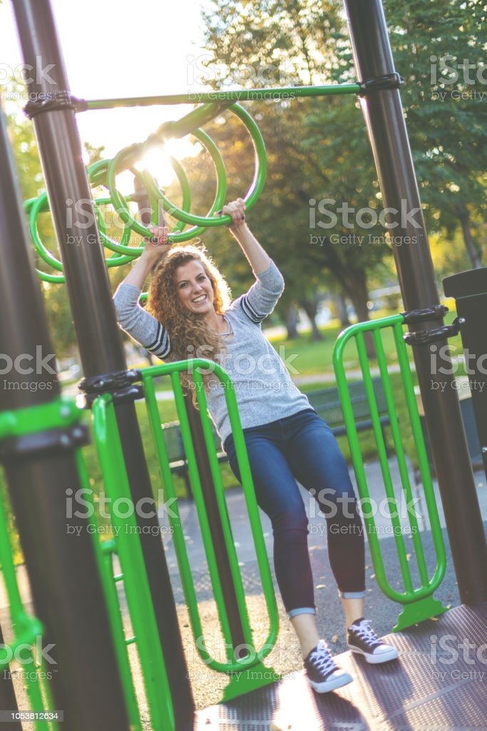 Young Adult Attractive Female College Student Early Autumn Fun in a Public Park stock photo