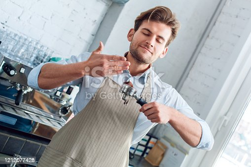 istock Young adult barista working in restaurant, smell freshly ground coffee 1212077428