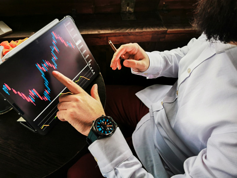 istock young adult bearded businessman with smart watch smoking cigar and touching his pro tablet screen checking market stock exchange for-ex block chain graphic 1170771921
