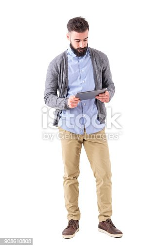 Young adult bearded hipster holding and watching at tablet computer. Full body length portrait isolated on white studio background.