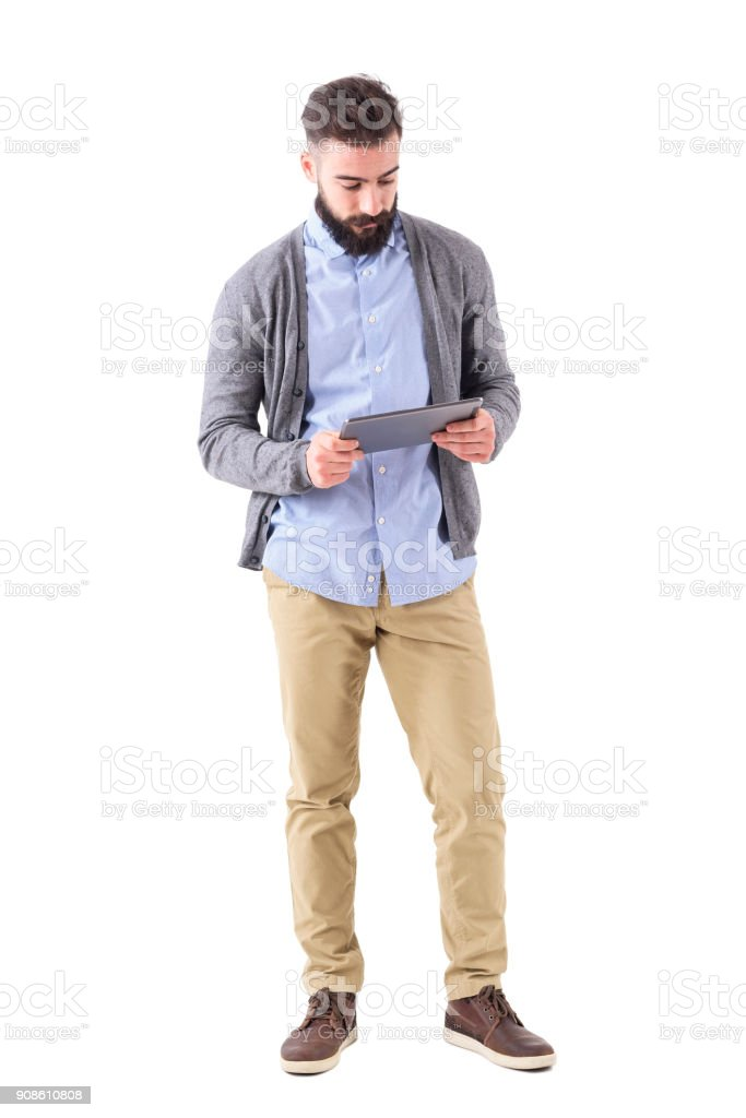 Young adult bearded hipster holding and watching at tablet computer. stock photo