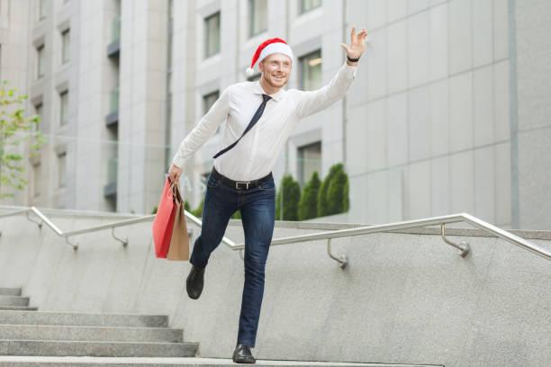junger erwachsener bärtiger mann in weihnachtsmütze hält viele einkaufstaschen und geschenke und laufen für kinder. - schnelles weihnachtsessen stock-fotos und bilder
