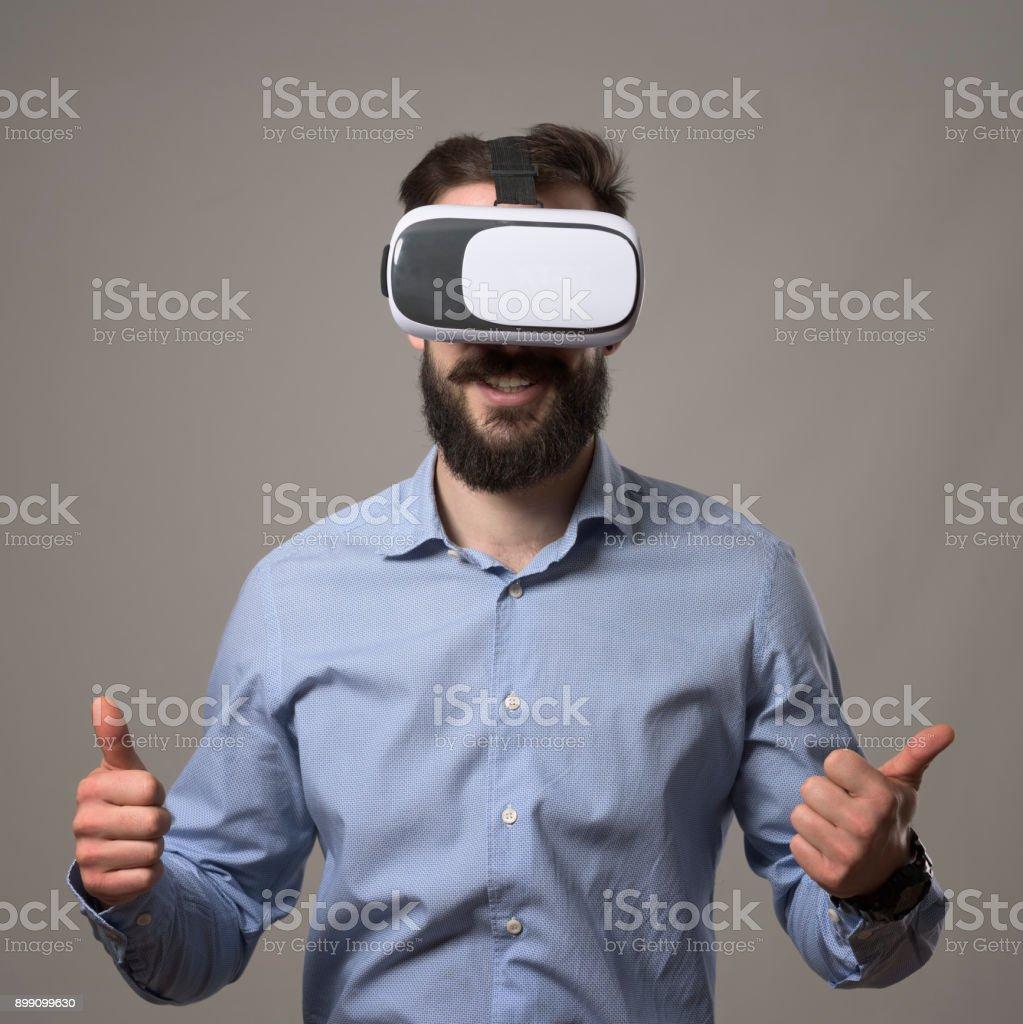 Jeune adulte barbu homme de vêtements de travail intelligente portant casque vr souriant avec les pouces vers le haut - Photo