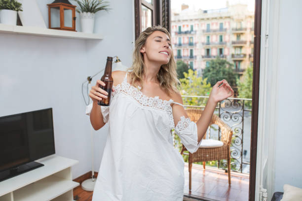 Young adult beautiful girl in casual clothes at home with a drink in a bottle stock photo