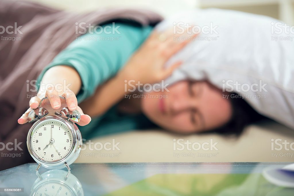 Young adult beautiful woman switching off alarm clock stock photo