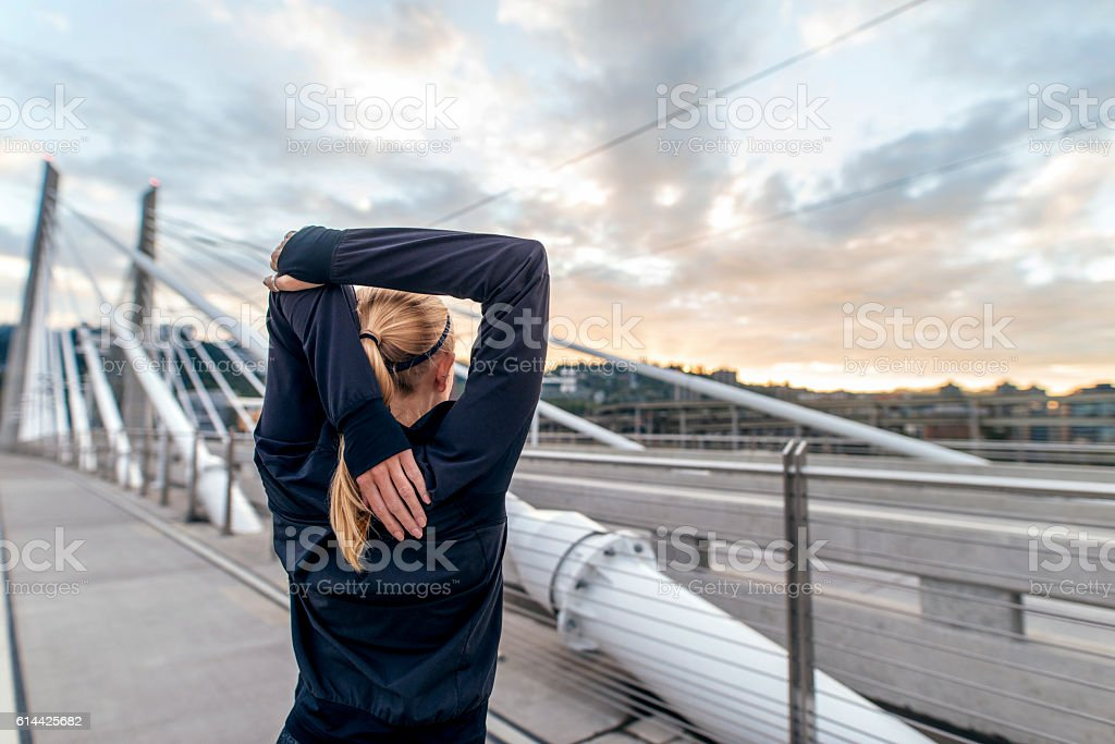 Young adult blonde female wearing a dark jacked and stretching stock photo