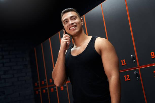 jonge volwassen bodybuilder die op moderne smartphone spreekt - call center stockfoto's en -beelden
