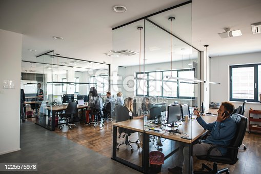 Young adult business colleagues interacting at communal workstations in see-through open plan office space.