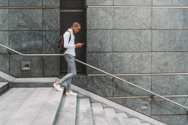 Young adult businessman in the city going down the stairs with smart phone stock photo