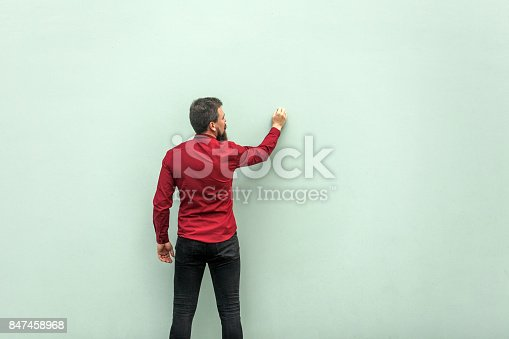 istock Young adult businessman painting on gray wall 847458968